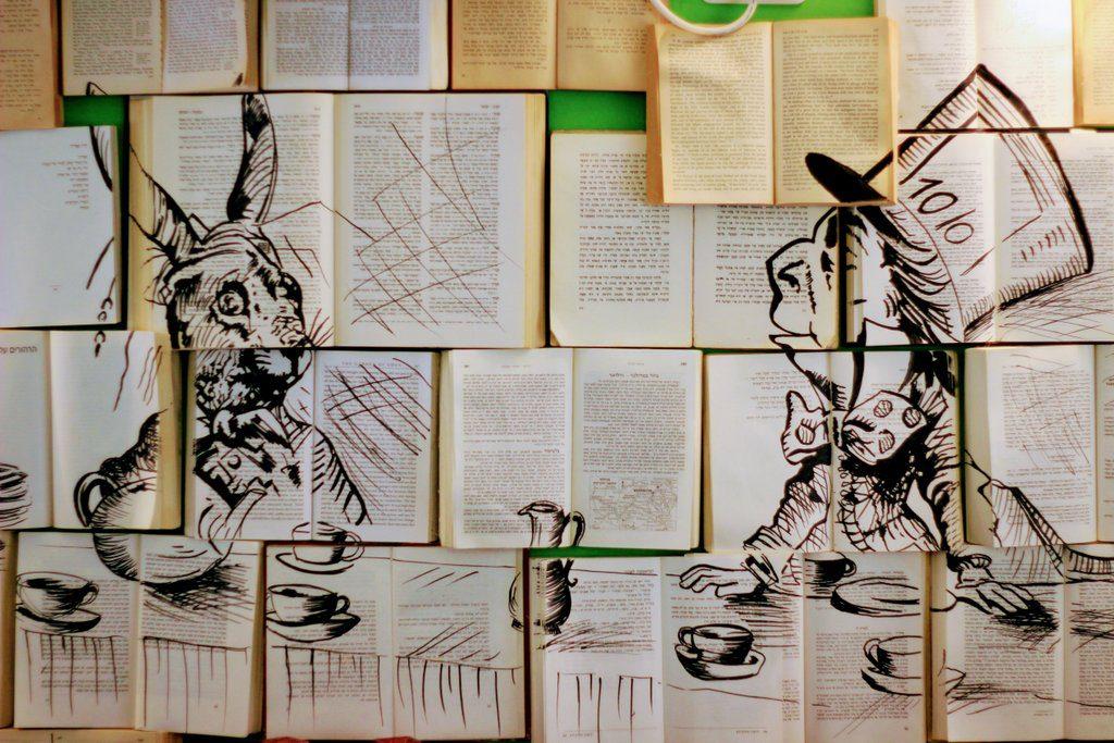 קיר מכוסה ספרים ועליהם ציור של אליס בארץ הפלאות