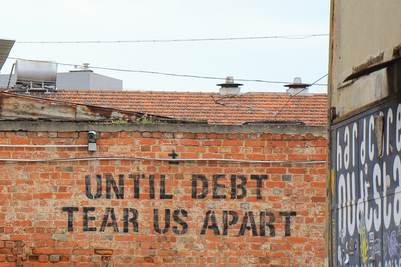a wall with text: until debt tear us apart