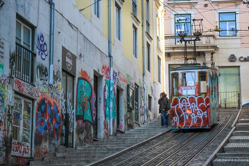 lisbon tram in a street with graphiti